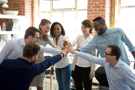 Photo for Excited multiracial colleagues give high five involved in teambuilding activity at meeting, happy diverse workers join hands celebrate success or win, show team spirit and unity. Cooperation concept - Royalty Free Image