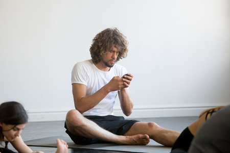 Photo pour Bored young man sitting texting a message using his mobile phone, having a break while group of young sporty people practicing yoga lesson, sitting not working out, indoor close up, yoga studio club - image libre de droit