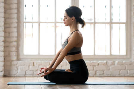 Photo pour Young sporty attractive woman practicing yoga, doing Ardha Padmasana exercise, Half Lotus pose, working out, wearing sportswear, black pants and top, indoor full length, white yoga studio, side view - image libre de droit
