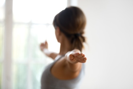 Photo pour Young sporty attractive woman practicing yoga, doing Warrior II exercise, Virabhadrasana 2 pose, working out, wearing sportswear, indoor close up back view, focus on fingers. Well being concept - image libre de droit