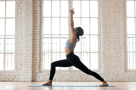Photo for Young sporty attractive woman practicing yoga, doing Warrior I exercise, Virabhadrasana 1 pose, working out, wearing sportswear, black pants and top, indoor full length, white yoga studio - Royalty Free Image