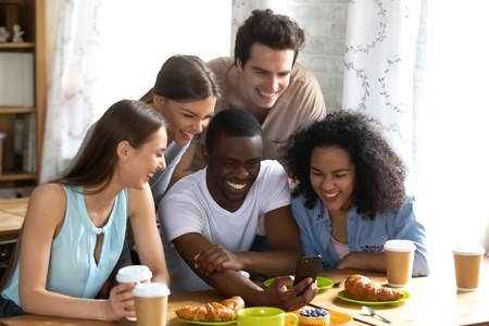 Photo pour Cheerful diverse multiracial millennial people sitting at table indoors watching funny entertainment videos. Black guy met with best friends having fun spends free time together taking a selfie photo - image libre de droit