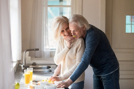 Photo for Senior loving husband hug wife from behind preparing food in kitchen, caring smiling aged woman feed beloved man while cooking at home, elderly couple have fun laughing making breakfast together - Royalty Free Image