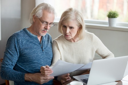 Foto de Serious aged husband and wife manage utility bills using laptop at home, concerned senior couple read bank loan or mortgage documents at kitchen table, elder man and woman check insurance paper - Imagen libre de derechos