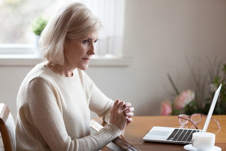 Photo for Thoughtful aged woman working at laptop thinking or considering something, doubtful senior female feel unsure pondering about solution, elderly lady sit at table lost in thoughts making decision - Royalty Free Image