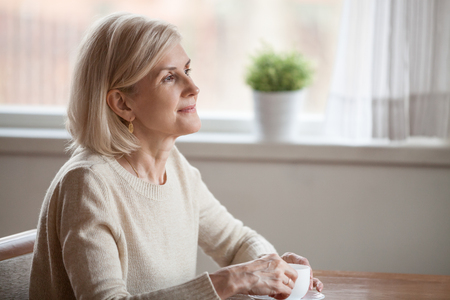 Photo pour Thoughtful senior woman drinking coffee or tea dreaming about something, dreamy aged female enjoying free time at home, thinking about pleasant memories, reminiscent elderly lady leisure morning - image libre de droit