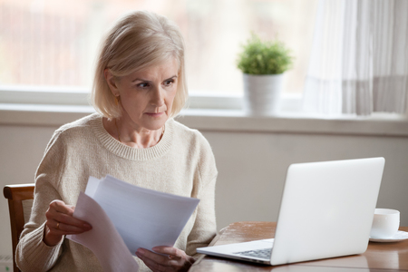 Foto de Serious aged woman holding documents, checking information at laptop online, concerned senior female managing bank insurance or loan papers, busy working at computer. Elderly and technology concept - Imagen libre de derechos
