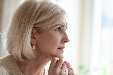 Photo pour Upset senior woman looking in distance remembering old times, sad aged female sit at home feeling lonely missing passed husband, elderly lady crying near window having difficult life situation - image libre de droit