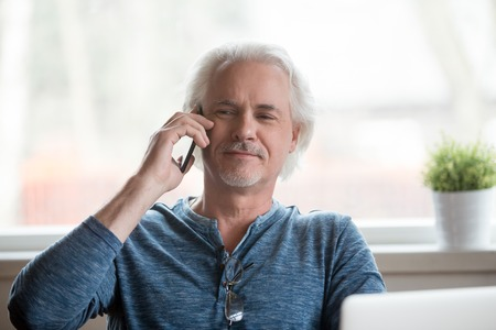 Photo pour Proud senior man talking on cell phone having pleasant conversation at home, satisfied aged male happy speaking over smartphone relaxing in chair. Elderly using new technologies concept - image libre de droit