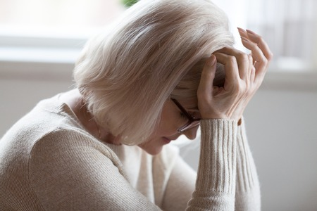 Foto de Tired elderly woman suffer from severe headache sitting with eyes closed, exhausted senior female feel unwell having strong pain or dizziness, upset aged lady in despair getting bad heartbreaking news - Imagen libre de derechos