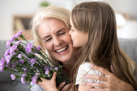 Foto de Little preschool granddaughter kissing happy older grandma on cheek giving violet flowers bouquet congratulating smiling senior grandmother with birthday, celebrating mothers day or 8 march concept - Imagen libre de derechos