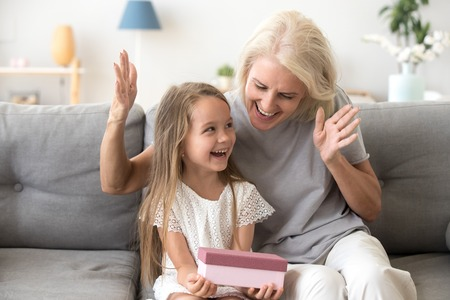 Foto de Excited grandchild happy to receive birthday present from loving old grandmother, smiling little kid holding gift box enjoys senior grandma surprise sitting on couch, granny congratulating child girl - Imagen libre de derechos