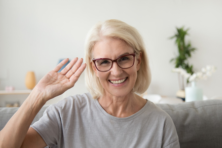 Foto de Smiling middle aged woman waving hand looking at camera, older mature lady in glasses making video blog or call at home, happy friendly senior vlogger sitting on sofa dating online, headshot portrait - Imagen libre de derechos