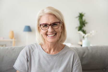 Foto de Smiling middle aged mature grey haired woman looking at camera, happy old lady in glasses posing at home indoor, positive single senior retired female sitting on sofa in living room headshot portrait - Imagen libre de derechos