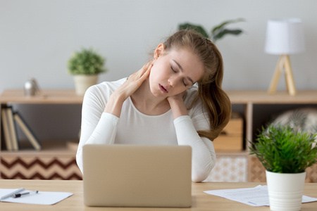 Photo pour Exhausted young female sit at home office desk massaging neck feeling ache, tired girl suffer from back pain or strain, having spasm symptoms, millennial woman feel unwell from sedentary lifestyle - image libre de droit