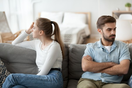 Photo pour Stubborn couple sit on couch back to back avoid talking after fight, offended man and woman separated on sofa ignoring one another, husband and wife not looking in eyes. Family conflict concept - image libre de droit