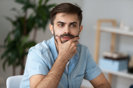 Foto de Close up of pensive millennial man sit at office home desk thinking of problem solution, thoughtful male lost in thoughts ponder or consider plan implementation, guy look in distance making decision - Imagen libre de derechos
