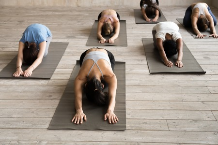 Photo pour Group of young sporty people practicing yoga lesson, doing Child exercise, Balasana pose, working out, indoor full length, female students training at club, yoga studio. Well being, fitness concept - image libre de droit