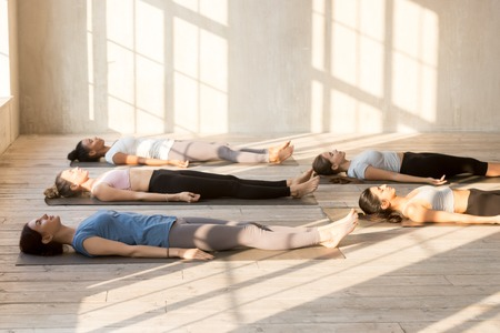 Foto de Group of young attractive people practicing yoga lesson doing Dead Body, Savasana exercise, Corpse pose, working out, indoor full length, mixed race female students training at club or yoga studio - Imagen libre de derechos