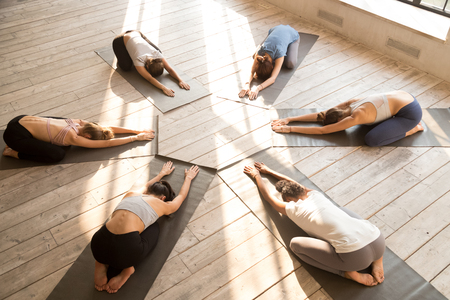 Photo pour Group of diverse young sporty people practicing yoga, doing Child exercise, Balasana pose, mixed race female students training at club, yoga studio, top view. Well being, wellness concept, full length - image libre de droit