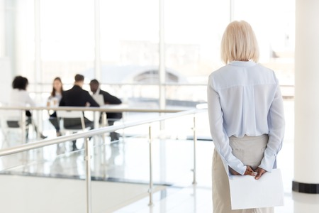Foto de Rear view at stressed nervous middle aged senior old business woman applicant waits for job interview holding papers behind back preparing for performance feel afraid of public speaking fear concept. - Imagen libre de derechos