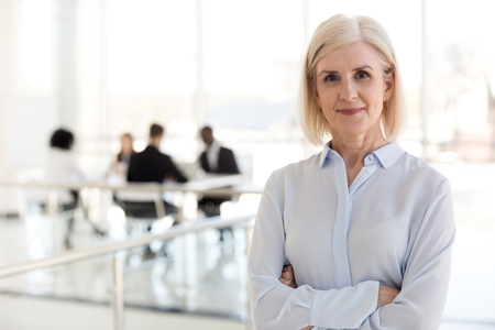 Foto de Confident mature businesswoman looking at camera, middle aged company ceo director, experienced senior female professional, old lady business coach team leader posing in office, headshot portrait - Imagen libre de derechos
