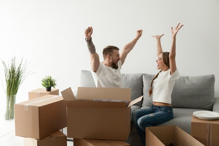 Photo pour Happy excited young couple sitting together on couch, sofa celebrating moving at new house with cardboard boxes with belongings, family just arrived in new home, man and woman start living together - image libre de droit