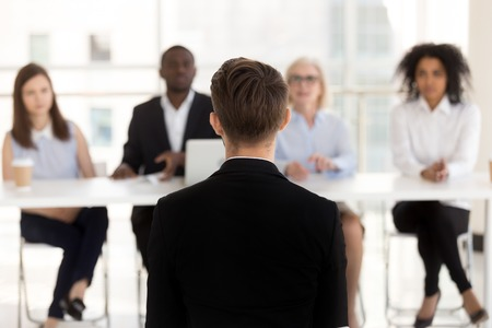 Photo for Rear view at man job seeker applicant during performance at interview with hr team, male vacancy candidate sits back talking making first impression on recruiters, human resources, employment concept - Royalty Free Image