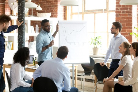 Foto de Confident smiling African American business coach speaking presentation to colleagues group at briefing, company meeting, explaining growth of sales graph, reporting about good result, motivating workers - Imagen libre de derechos