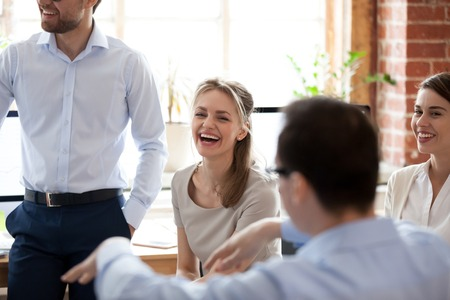 Foto de Happy laughing businesswoman at briefing, company meeting with group, team colleagues, office workers brainstorming together, discussing funny news, celebrating good results, good relationships in team - Imagen libre de derechos