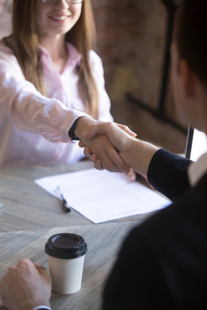 Photo for Friendly attractive young woman handshaking man at meeting. Deal with good result, start of work with business partner or customer, good relationship, recruitment, hiring process, HR concept. Close up - Royalty Free Image