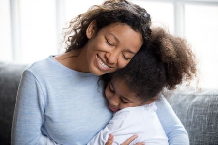 Foto de Loving African American mother embracing with preschooler little adorable daughter, sitting together on couch at home, warm relationships parent and child, closeness, love and support concept - Imagen libre de derechos