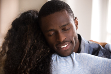 Foto de Calm loving African American husband embracing wife with closed eyes, affectionate couple in love, romantic relationship, loving man supporting woman rear view, gratefulness, close up - Imagen libre de derechos