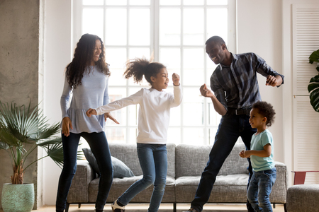 Photo for Happy African American having fun together indoors, funny married couple dancing with adorable little preschooler daughter and cute toddler son at home, listening to music, family weekend with kids - Royalty Free Image