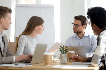 Photo for Millennial diverse employees talk brainstorming or collaborating at office meeting, workers sit at shared table with laptops cooperating at casual briefing, colleagues analyze statistics or paperwork - Royalty Free Image