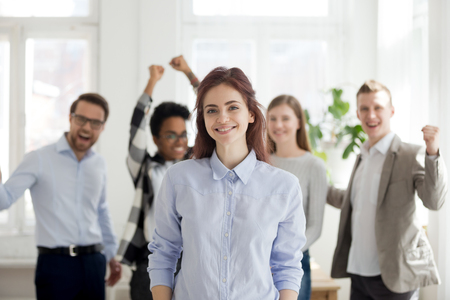 Foto de Portrait of smiling female employee standing foreground, excited team or colleagues cheering at background, successful woman professional look at camera posing in office. Leadership concept - Imagen libre de derechos