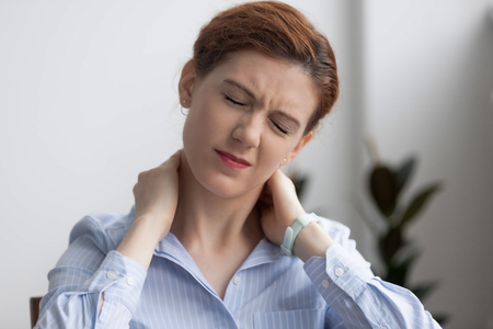 Photo pour Head shot woman writhing in pain suffering from neck pain at work in office. Fatigued female touching massaging sore neck feels unhealthy. Sedentary lifestyle, long time working without break concept - image libre de droit