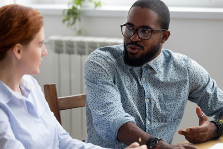 Photo for Diverse business people sitting at desk during meeting, black company owner talking with female investor discuss startup business plan. Multiracial colleagues take break having informal conversation - Royalty Free Image