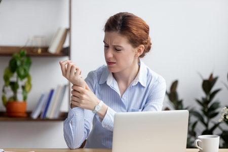 Foto de Businesswoman sitting at desk in office touch wrist feels pain. Unhealthy upset female having carpal tunnel syndrome because of active and long-term use of the keyboard and mouse in the wrong posture - Imagen libre de derechos