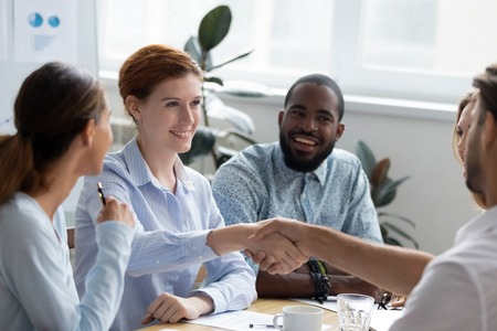 Photo for Businesswoman company executive manager sitting with colleagues handshaking with client gathered together in boardroom. Business people welcoming experienced business coach starting seminar training - Royalty Free Image