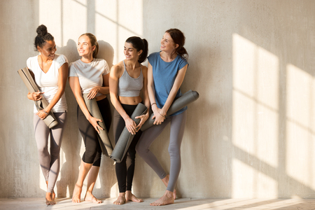 Foto de On a sunny morning beautiful diverse girls gathered at gym for workout. Four slim women in sportswear standing barefoot near wall holding yoga mats talking feels happy. Group training wellness concept - Imagen libre de derechos