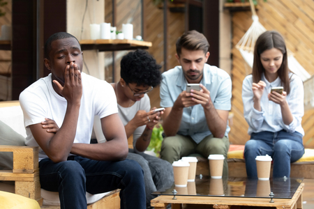 Photo pour Bored African American man sitting with people with phone dependence, yawning, friends using mobile devices, apps, looking at screen, ignore each other in cafe, smartphone addiction concept - image libre de droit
