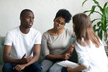 Photo pour Unhappy young African American couple visiting psychologist, upset man talking about relationships problem with tired frustrated woman, family therapy session, husband and wife sit on couch together - image libre de droit