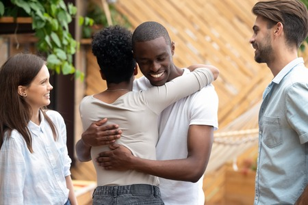 Photo pour Happy meeting of young African American couple in love embracing in cafe, greeting, hugging each other, shy caucasian friends, sister and brother in good relationships, friendship concept - image libre de droit