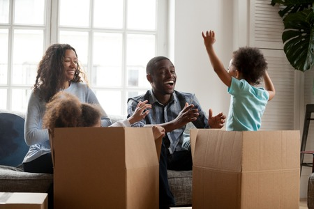 Foto de Excited mixed race kids jumping out of box playing with mom dad in living room, african joyful children having fun laughing packing unpacking with black parents, family moving in new home relocation - Imagen libre de derechos