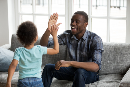 Photo for Happy black dad and little son giving high five playing at home, excited african single father and toddler cute kid boy laughing enjoying clapping hands having fun together, daddy child friendship - Royalty Free Image
