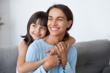 Foto de Happy family of smiling single mom and cute kid daughter embracing looking into bright future thinking of good, little child girl embracing young loving mother dreaming planning new goals concept - Imagen libre de derechos