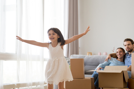Foto de Cute small kid feels happy playing on moving day concept, active happy girl running over living room exploring new apartment, excited child having fun in modern home with parents after relocation - Imagen libre de derechos