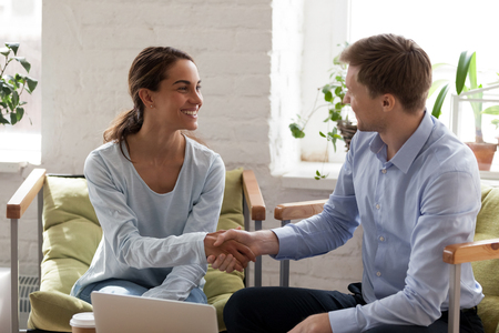 Foto de Smiling happy woman shaking hand of confident businessman, getting acquaintance with new business partner, making deal, greeting, introducing to client, successful negotiation, agreement - Imagen libre de derechos