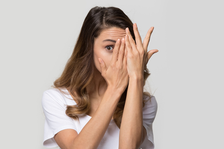 Photo pour Young curious woman covering face with hands peeping spying eye on white studio wall, funny girl feeling afraid fear shy hiding looking at camera through fingers isolated on light blank background - image libre de droit